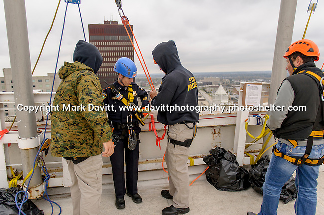 """For the big, 345-ft. rappel, Captain Kramer from the Pleasant Hill Police Department gets ready with the help of experts to go """"Over the Edge"""" of the Financial Center in Des Moines for Special Olympics Iowa Oct. 26."""