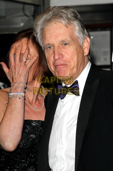 guest & Nick Owen.Daily Mail Inspirational Woman of The Year Awards at the Marriott Grosvenor Square Hotel, London, England..January 18th, 2012.half length black strapless dress tuxedo nicholas funny hand covering face.CAP/ROS.©Steve Ross/Capital Pictures