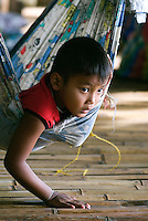 A young boy rests in a hammock at his families bungalow hotel in Khao Sok National Park in southern Thailand. Floating bamboo bungalows are the only accommodations in remote areas of the largest protected forest on the Thai-Malaysian peninsula. Often the owner's entire family with live and work at the bungalows. .