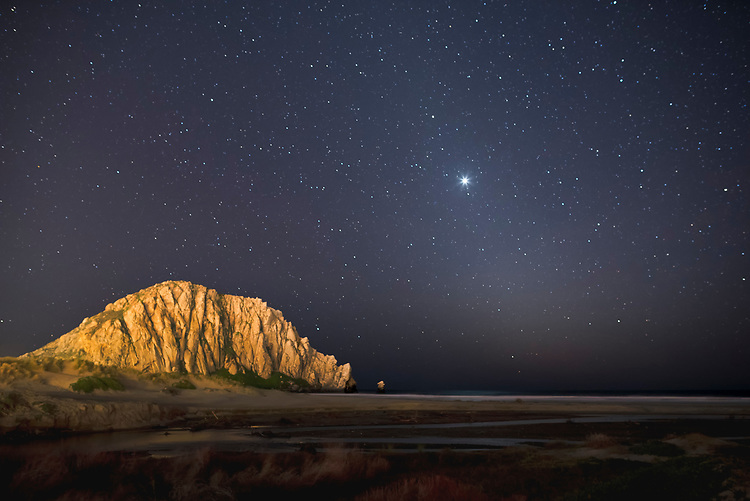 This star and planet filled night sky is anchored in the foreground by Morro Rock which is illuminated by the nearby lights of Morro Bay's small harbor.