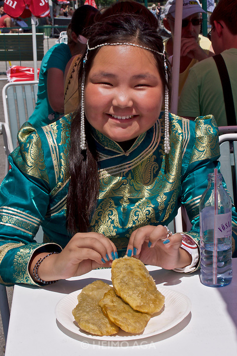 Baden bei Wien, Lower Austria. Naadam Festival of OTSCHIR (Austrian-Mongolian Society) at the Trabrennbahn.<br /> Girl in traditional dress eating Chuushuur (Mongolian dumplings).