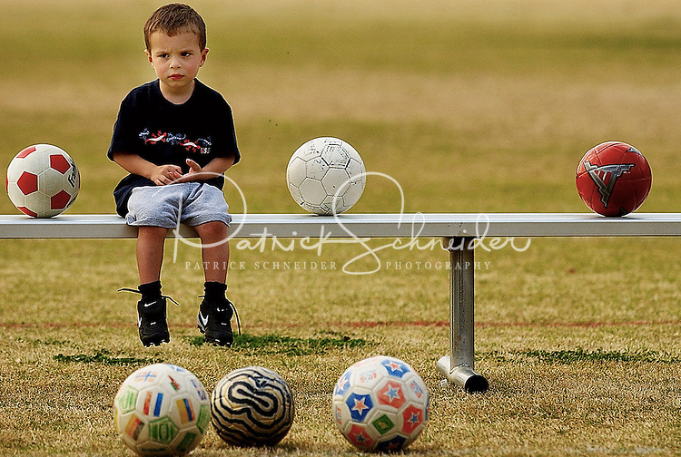 A young boy wishes he could play soccer as he waits during his brother's soccer practice with a youth soccer league in Charlotte, NC