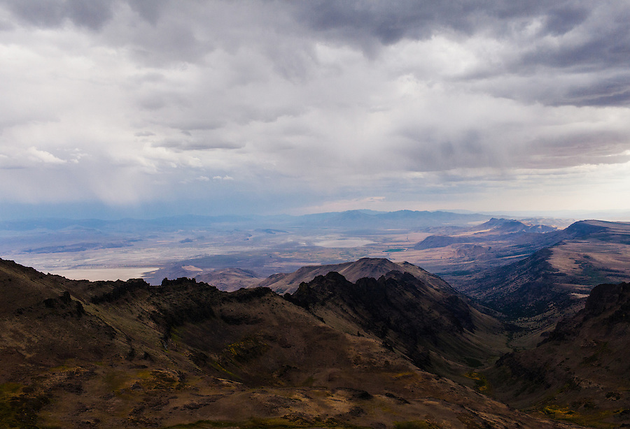 Bands of rain follow the storm clouds in the Southeast Oregon basin near the edge of the Alvord Desert, seen from Steens Mountain.