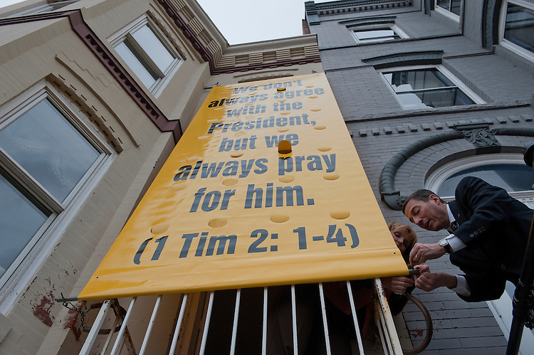 "UNITED STATES - Jan 17 : Peggy Nienaber and Rev. Rob Schenck of Faith and Action secure a banner at the Faith and Action building. Clergy leaders put the banner up today on their building which reads, ""We don't always agree with the President, but we always pray for him. (1 Tim 2:1-6)."" The banner will hang from the Ostrowski House and remain on display until January 27.  (Photo By Douglas Graham/CQ Roll Call)"