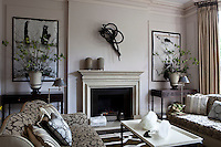 The living room has a neutral colour palette and is decorated with a collection of contemporary sculpture and artworks