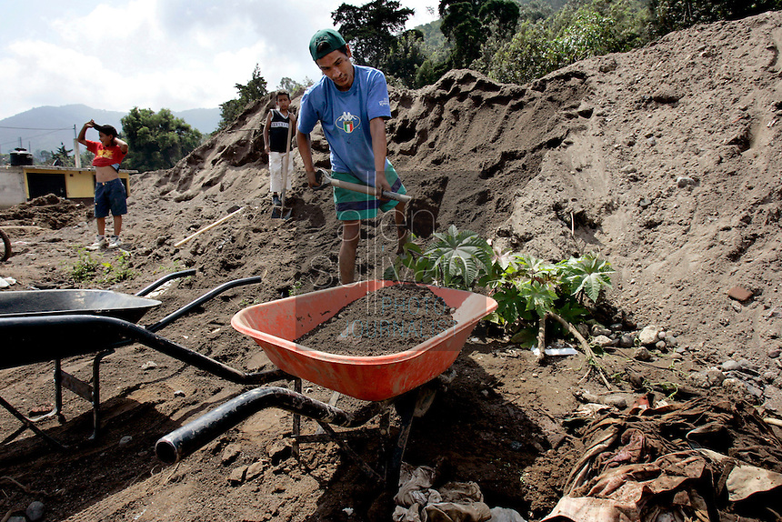 Erick Rosales shovels sand and mud in Jocotenango, Sacatapequez, Guatemala on Friday, Oct. 21, 2005 that collected after a nearby river flooded in early October during heavy rains associated with Hurricane Stan, sending water and mud several feet high through Jocotenango and destroying several homes, including that of Rosales and his family. Rosales, a former Los Angeles, Calif. gang member who returned to Guatemala two years ago to escape gang life, said he will try to sell the sand to road builders in order to make a meager living. Torrential rains and mudslides killed or made missing thousands of Guatemalans in early October.<br />