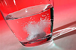 Tablet effervescing as it dissolves in a glass of water against a red background. Royalty Free