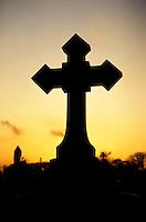 Silhouette of a religious cross at sunset, Père Lachaise Cemetery, Paris, France.