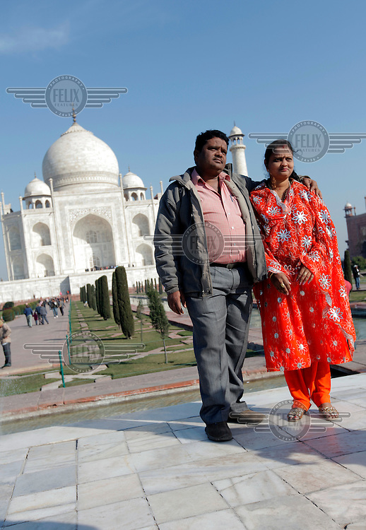 "A couple having their picture taken. The Taj Mahal , also ""the Taj"", is a mausoleum. It was built by Mughal emperor Shah Jahan in memory of his third wife, Mumtaz Mahal..Taj Mahal is an example of Mughal architecture, a style that combines elements from Persian, Islamic and Indian architectural styles..In 1983, the Taj Mahal became a UNESCO World Heritage Site."