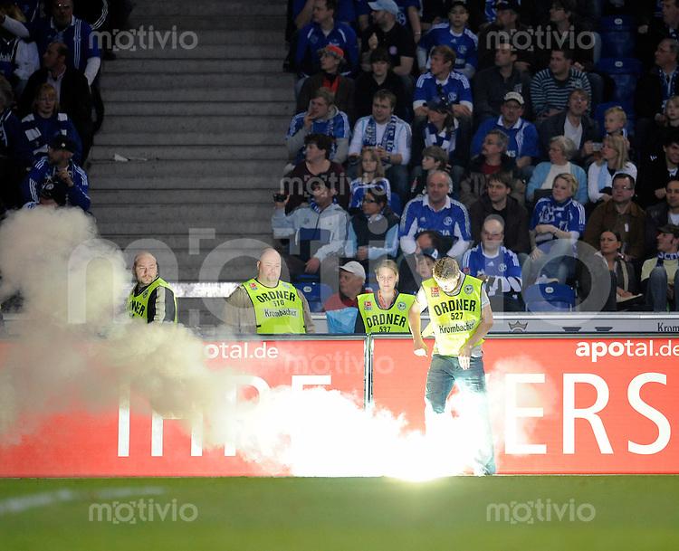 Fussball    1. Bundesliga    Saison 2008/2009    26. Spieltag     Arminia Bielefeld - FC Schalke 04         03.04.2009  Ein Ordner versucht eine Leuchtrakete zu loeschen.