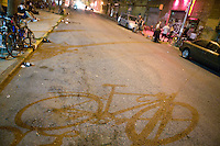 30 June 2005 - Brooklyn, NY, USA - The shadow of a bike stretches across the street outside a bar in Brooklyn, USA, June 30th 2005, where riders have gathered ahead on the first evening of the 13th annual cycle messenger world championships. More than 700 riders from all over the world took part in the 4-day competition which carries event based on the daily work of a city bike messenger.
