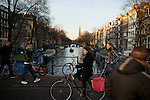 People cross the Berenstraat bridge over the Prinsengracht in downtown Amsterdam.