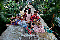 Bangladeshis sleep on the roof of a moving train as they rush home to their respective villages to be with their families in Mymensingh, near Dhaka, Bangladesh.