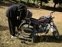A foot soldiers from the Wardak Mobile Patrol Unit repairs a puncture on his chinese motorcycle armed with AK47 Kalashnikov