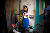 "15 year old Nasridah, a student at Kartini Emergency School, washes clothes in the slum neighbourhood where she lives. Unable to continue her studies in her village due to economic constraints, Nasridah came to Jakarta in early 2007 to work as a domestic worker. She says, ""One day while I was watching the television, I saw news about the 'Twin Teachers' and their free emergency school. I was very excited and decided to look for the school. Upon meeting the twins I asked them if I could study there and they accepted me. Because I don't have a home in Jakarta, the twins found me a family in the slum area near the school who were willing to let me stay in their home for free in exchange for some household chores such as washing and ironing clothes. When I complete my high school study I would like to work in a Salon."" Since the early 1990s, twin sisters Sri Rosyati (known as Rossy) and Sri Irianingsih (known as Rian) have used their family inheritance to set up and run 64 schools in different parts of Indonesia, providing primary education combined with practical skills to some of the country's most deprived children."
