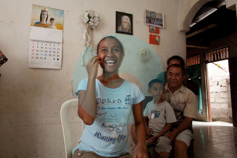March 15th, 2009_DILI, TIMOR-LESTE_ 19 year old Octaviana do Rosario Barros Faria (blue shirt) reacts to hearing the news of her new found overseas scholarship, while posing with her family for a photograph in their home near the Timorese capital city of Dili.  Octaviana was one of four students chosen this year by the Blair Forester Memorial Trust for an overseas scholarship award.  Photographer: Daniel J. Groshong/Tayo Photo Group
