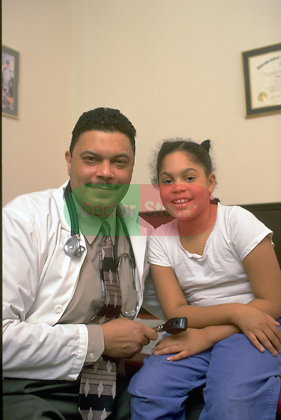 portrait of doctor sitting with smiling girl patient