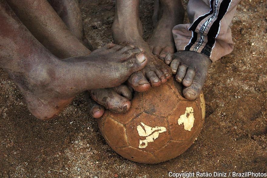 Soccer in Rio de Janeiro favela, black shoeless poor boys play soccer at Favela Dois Irmaos, Brazil.