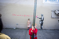 """Parents bring their children to the Woodside neighborhood of Queens in New York on Monday, October 14, 2013 to see the fourteenth installment of Banksy's graffiti art, """"What we do in life echoes in Eternity"""". The elusive street artist is creating works around the city each day during the month of October accompanied by a satirical recorded message which you can hear by calling the number 1-800-656-4271 followed by  # and the number of artwork.  (© Richard B. Levine)"""