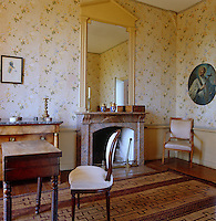 This bedroom is decorated with floral wallpaper with a simple marble fireplace and a painted mirror