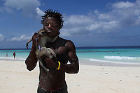 A young man and his pet monkey are photographed on the beach in Nungwi, Tanzania.