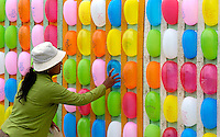 Images from the Book Journey Through Colour and Time During the annual boat races in Phnom Penh Cambodia, festivities are held, like trowing darts at these colorful balloons, for a small prize.The poor peoples entertainment