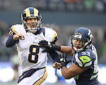 St. Louis Rams quarterback Sam Bradford  passes under pressure from Seattle Seahawks linebacker Malcolm Smith at CenturyLink Field in Seattle, Washington on December 30, 2012.   Bradford completed 25 of 42 passes for 252 yards, passed for one touchdown and threw one interception in the Rams 13-20 loss to the Seahawks.  © 2102.  Jim Bryant Photo. All Rights Reserved.
