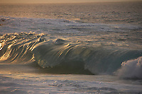 Pitching shorebreak lit up by the sunset at Ke Iki Beach on the North Shore of O'ahu.