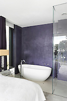 A purple bedroom with a freestanding bath and a shower within a glass cubicle in the room.