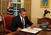 Washington, DC - June 23, 2009 -- United States President Barack Obama signs the Supplemental Appropriations Act in the Oval Office of the White House in Washington, DC, USA 24 June 2009. The signing adds military funding for the wars in Iraq and Afghanistan.   .Credit: Mike Theiler / Pool via CNP