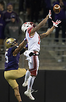 Demari Simpkins skies for a catch in front of Husky cornerback Myles Bryant.