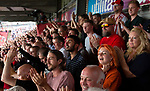 Home supporters cheering their team's second goal from the Ealing Road terrace as Brentford hosted Leeds United in an EFL Championship match at Griffin Park. Formed in 1889, Brentford have played their home games at Griffin Park since 1904, but are moving to a new purpose-built stadium nearby. The home team won this match by 2-0 watched by a crowd of 11,580.