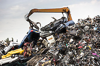 Grab machine moving scrap metal, cars and autos for metal recycling to avoid environmental pollution in England