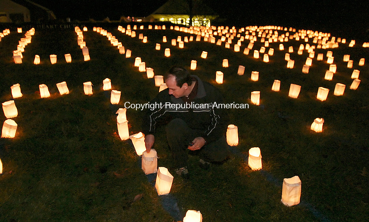 SOUTHBURY, CT 01/01/08-010108BZ02- Tom Meyer of Southbury, lights luminaries to form the word &quot;HOPE&quot; on the lawn outside Sacred Heart Church in Southbury Tuesday night.   The vigil was in remembrance of youth from the area who had untimely deaths recently.<br /> Jamison C. Bazinet Republican-American