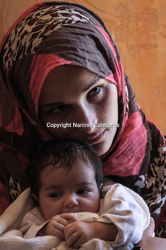June 11, 2015 - Bekaa Valley, Lebanon: Hamda Saleh, a Syrian refugee woman holds her baby inside a tent in a temporary shelter settled in Saadnayel city in east of Lebanon. Her baby was born stateless after she fled from Homs, her hometown, when opposition armed groups started battling against the government of President Bashar Al-Assad. (Photo/Narciso Contreras)