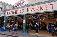 Neon signs and people entering the Pike Place Public Market, Seattle, Washington state, USA
