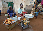 A woman cooks food to sell in a camp for more than 12,000 internally displaced persons located on the grounds of the Roman Catholic Cathedral of St. Mary in Wau, South Sudan. Most of the families here were displaced in June, 2016, when armed conflict engulfed Wau.<br /> <br /> Norwegian Church Aid, a member of the ACT Alliance, has provided relief supplies to the displaced in Wau, and has supported the South Sudan Council of Churches as it has struggled to mediate the conflict in Wau.