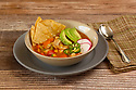 Mexican tortilla soup with chips, radishes, jalapeno peppers and chicken in tomato broth