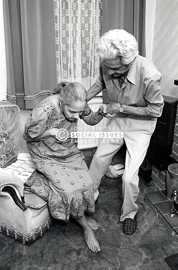 Elderly Asian man caring for his wife, Nottingham UK 1991