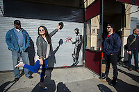 """Street art enthusiasts flock to Larry Flynt's Hustler Club in the Hells Kitchen neighborhood of New York on Thursday, October 24, 2013 to see """"Waiting in vain""""  the twenty-fourth installment of Banksy's graffiti art. The stenciled artwork is on the roll-up gate at the entrance to the gentlemen's club, which has posted security guards outside to protect their new masterpiece.  The elusive street artist is creating works around the city each day during the month of October called """"Better Out Than In"""".  (© Frances M. Roberts)"""