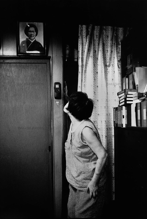 Yuriko looks up at the photograph of her mother. Her mother died from cancers due to the atomiic bomb. Her mother was pregnant with Yuriko when the bomb hit her...August 2002.