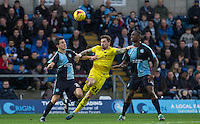 Chris Maguire of Oxford United holds off Luke O'Nien of Wycombe Wanderers & Anthony Stewart of Wycombe Wanderers during the Sky Bet League 2 match between Wycombe Wanderers and Oxford United at Adams Park, High Wycombe, England on 19 December 2015. Photo by Andy Rowland.