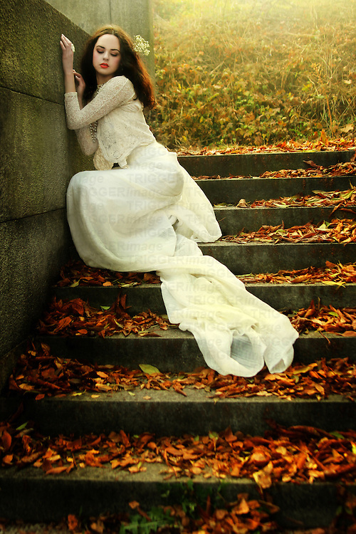A pretty brunette in a white gown sitting on the stairs covered with autumn leaves.