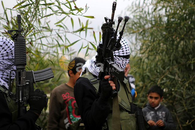 Palestinian gunmen of the al-Aqsa Martyrs' Brigades march during a military parade to mark the 50th anniversary of the Fatah movement in the Qalandia refugee camp near the West Bank city of Ramallah, January 1, 2015. Yasser Arafat founded Fatah in 1965 with the goal of destroying Israel. The party rose to prominence in the 1970s and '80s with a series of hijackings and other attacks. Over time, Fatah moderated and accepted Israel's right to exist, while seeking a Palestinian state. Arafat died in 2004. Photo by Shadi Hatem