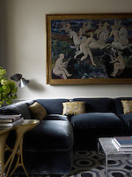 A painting by Carlo de Roover in the study hangs above an L-shaped sofa designed by Steven Volpe