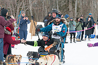 Quince Mountain and team run past spectators on the bike/ski trail near University Lake with an Iditarider in the basket and a handler during the Anchorage, Alaska ceremonial start on Saturday, March 7 during the 2020 Iditarod race. Photo © 2020 by Ed Bennett/Bennett Images LLC