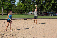 A young fit male serves volleyball during tournament at Zilker Park sand volleyball courts in Austin, Texas.