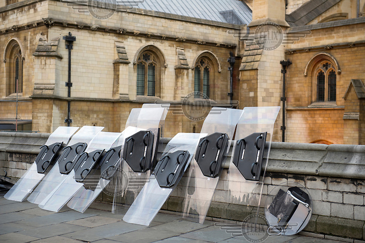 Riot police shields leaning against a wall by the Houses of Parliament in London during a demonstration by students against the government's proposed increase in university tuition fees.