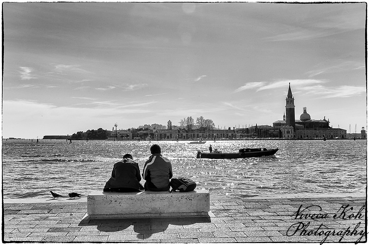 Two people sitting on a stone bench in front of Venetian canal in Venice, Italy, with boat and Campanile San Giorgio in background.