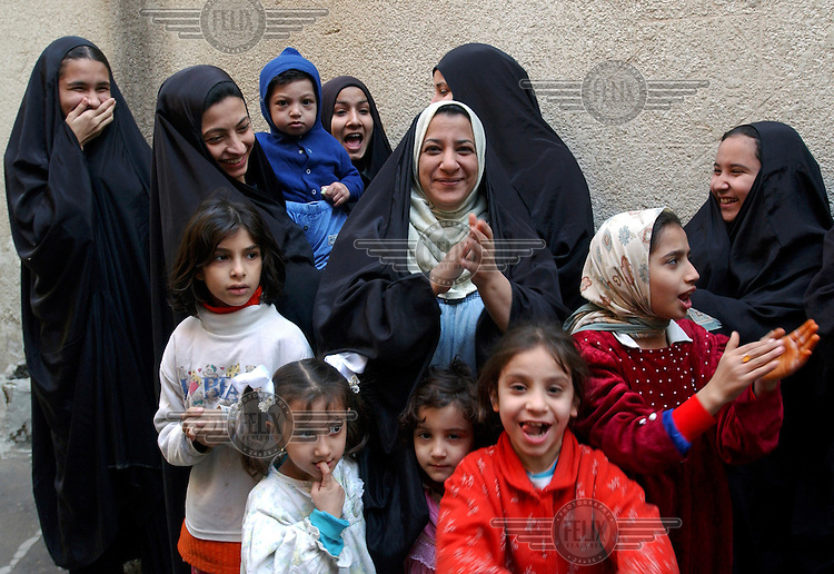 Women in the streets of Ju'aifir express their happiness, following the news that ex-President Saddam Hussein had been captured by American forces.